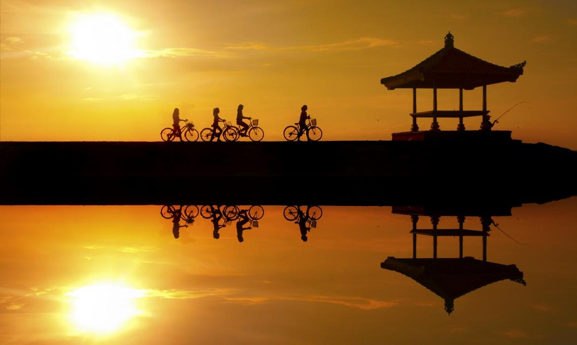 Reflection of cyclists riding on a concrete barrier in Sanur beach at sunrise