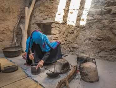 Omani woman in traditional outfit preparing coffee, Al Hamra